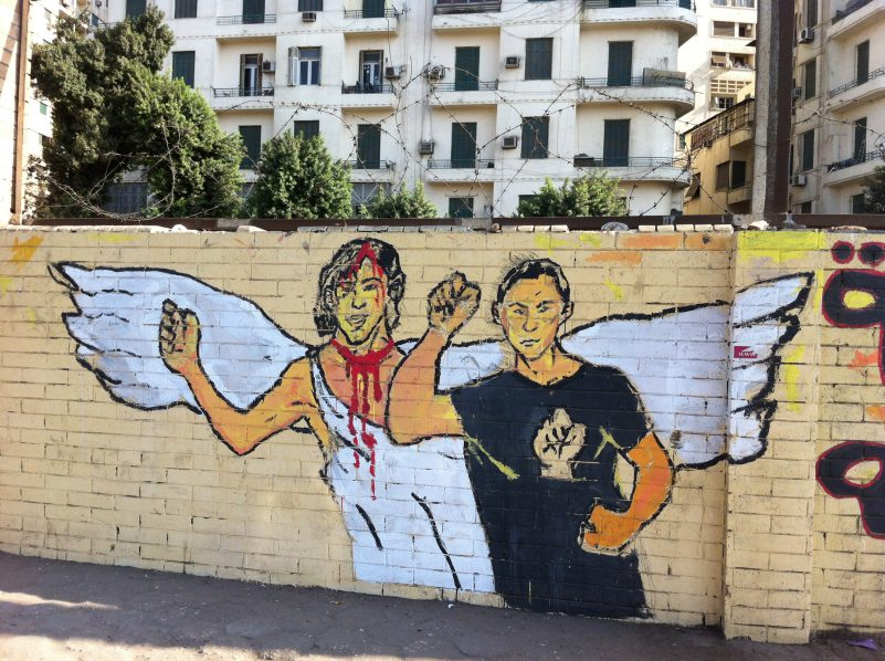 A slain revolutionist with her or his living counterpart on a wall near Tahrir Square, Cairo, Egypt